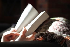 picture of a woman reading under a blanket