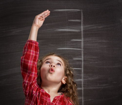 Photo of a little girl looking up with a height chart behind her