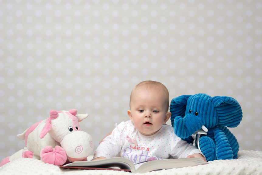 image of a baby girl reading a book with friends